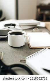 Coffee cup on home office desk workspace with stationery.