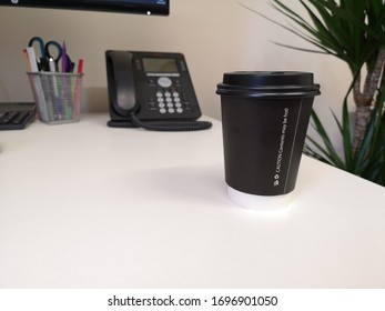 Coffee cup on an office desk with a phone and pencil holder