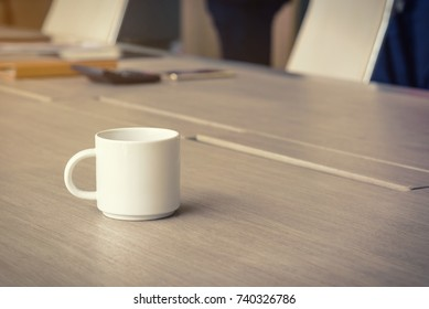 coffee cup on the office desk and business office background concept, selective focus