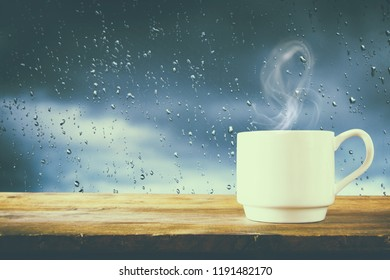 coffee cup on a rainy day over wooden table and window with rain drops background