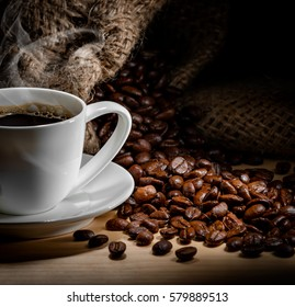 Coffee. Cup of coffee on the table with coffee beans