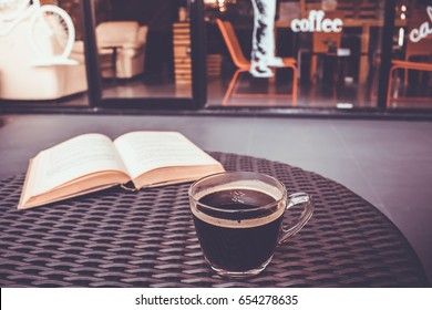 Coffee cup on table with book ,coffee shop background