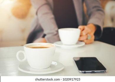 Coffee cup on table in cafe shop. Woman  having chill time with coffee in coffee shop.