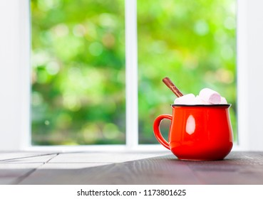 Coffee cup on table in cafe with blur green garden