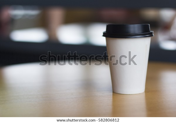 Coffee cup on table. Coffee and chocolate bar. Paper coffee cup.White carton cup.