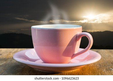 coffee cup on the table has a mountainous background and sunrise.