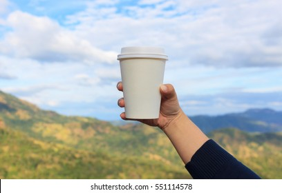 coffee cup on women hand with mountain and blue sky background