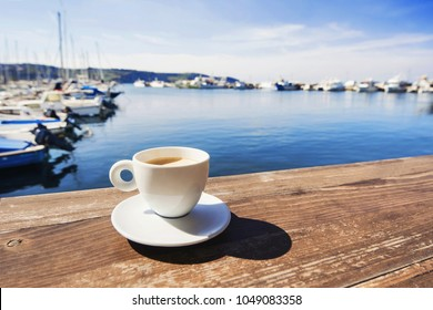 Coffee cup on a wood table over blue sky and sea background. Summer holiday concept