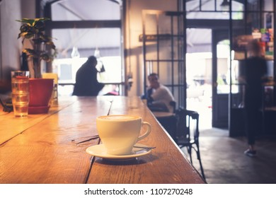 coffee cup on wood table in cafe interior