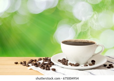 Coffee cup on wood table and green natural background., With copy space.