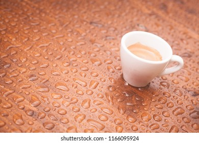 A coffee cup on a wooden platform with rain drops.