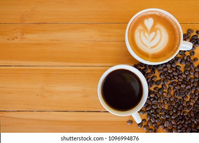 Coffee cup on wooden table background. Freshly brewed coffee in a restuarant. Hot black coffee with hot cappuchino in a coffee bar.