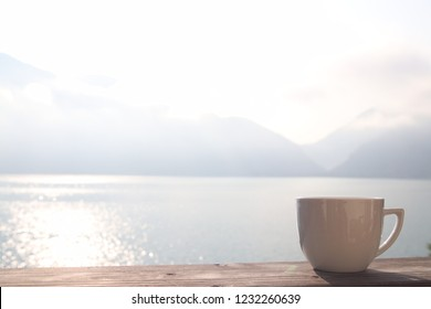 A coffee cup on a wooden table pictured on a bright summer morning with a lake and mountains in the background. Taken at Attersee, Austria.