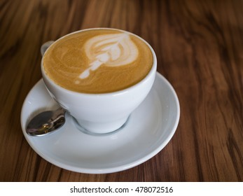 Coffee cup on a wooden table with spoon, selective focus