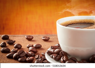 Coffee cup on a wooden table with coffee beans