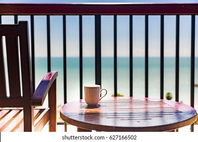 coffee cup on wooden table and chair at balcony with sea view, concept of relaxing and vacation