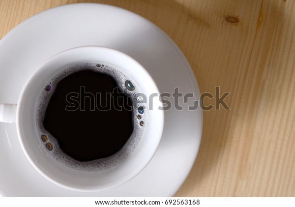 Coffee cup on wooden table,Top view.