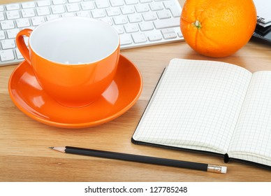 Coffee cup, orange fruit and office supplies on wooden table
