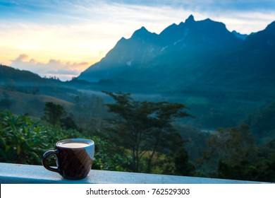 coffee cup over blurred image of dao mountain view,Chiang Mai,Thailand.