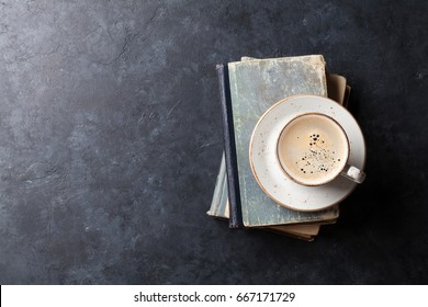 5600db680156 Coffee cup over books on stone table. Top view with space for your text
