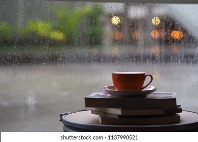 A coffee cup over window glass with water drop background.