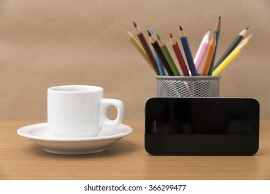 coffee cup and phone with color pencil on wood background