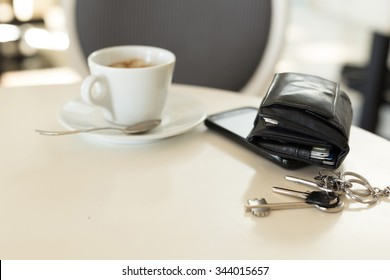 Coffee cup with phone and leather wallet on table