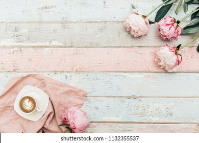 Coffee cup and pink peony flowers on  shabby chic table. top view in flat lay style.