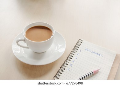 coffee cup  is placed on the table  And a workbook is placed next to it.