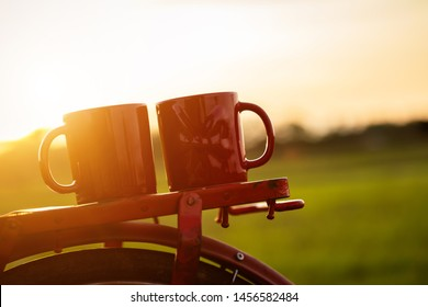 Coffee cup put on the Red Japan style classic bicycle at view of green rice field in sunset time