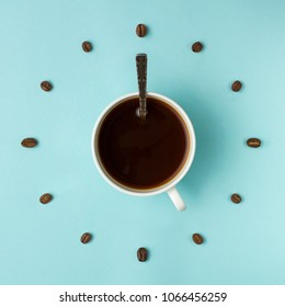 Coffee cup and roasted beans arranged as clock face on blue background, top view. Coffee time symbol. Interesting idea energy and refreshment concept.