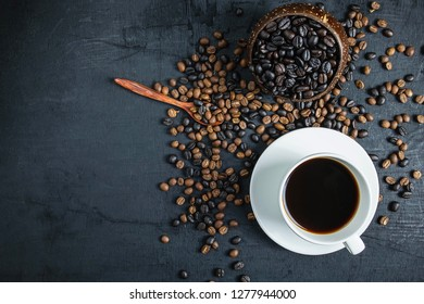 Coffee cup and roasted coffee beans On a black background