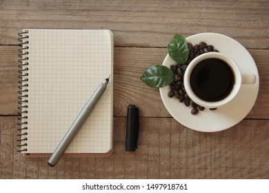 Coffee cup with roasted brown beans, green leaves and blank notebook on wooden table, empty space for your text. Flat lay composition. Close up, top view, background.
