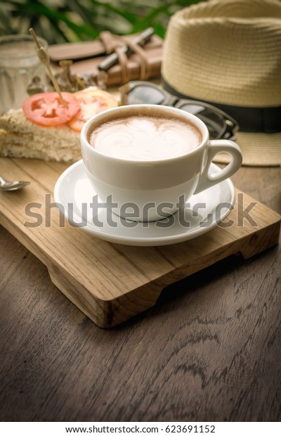 Coffee cup and sandwiches on a wooden table.