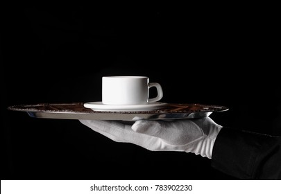 Coffee cup and saucer on silver tray being served by white gloved person