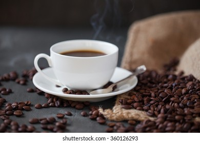 Coffee cup and saucer on a wooden table. Grey background.