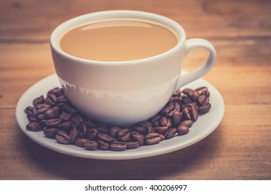 Coffee cup and saucer on a wooden table. Dark background.