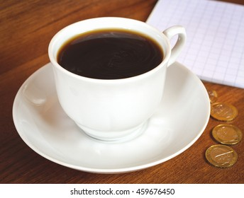 Coffee cup and saucer on a wooden table. Dark background and money with blank.