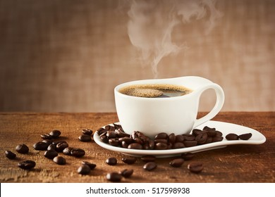 Coffee cup and saucer on a wooden table with coffee beans