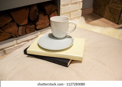 Coffee cup with saucer placed on books and pillow near firewood - cosy home