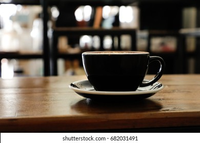Coffee cup in coffee shop on wooden table.