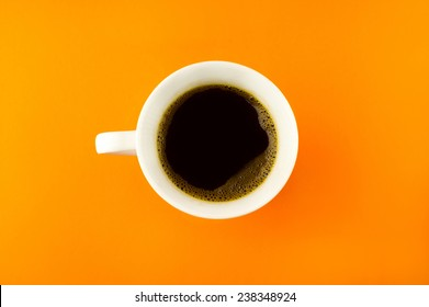 A coffee cup shot from above on a bright orange background.