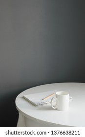 coffee cup with sketchpad and pencil on white wooden table in scandi kitchen interior, vertical stock photo image with copy space for text