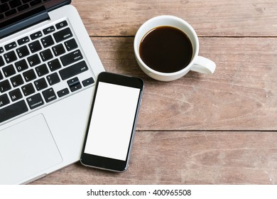 Coffee cup smart phone and laptop on old wooden table