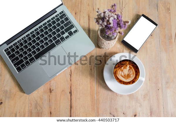 Coffee cup smart phone and laptop on wood table. View from above