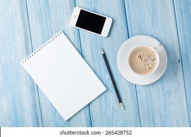 Coffee cup, smartphone and blank photo frame on wooden table background. Top view with copy space