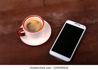 Coffee cup and smartphone on wooden table. View from above