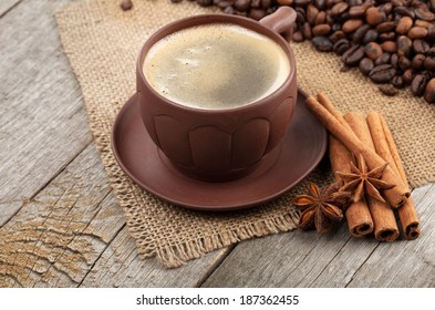 Coffee cup with spices on wooden table texture