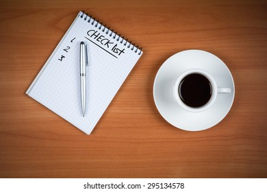 Coffee cup, spiral notebook with CHECK LIST text and pen on the wooden table