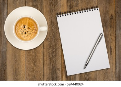 Coffee cup, spiral notebook and pen on the wooden table. Top view.